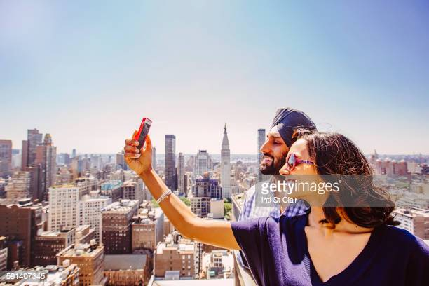 Indian couple taking selfie over New York cityscape, New York, United States