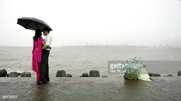 Indian couples enjoy the view durign a rainshower across The Arabian Sea from Mumbai on June 11 2008 The monsoon season which runs from June to...