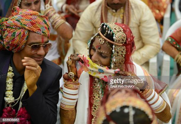 Indian couples in traditional outfits take part in a mass wedding ceremony on the outskirts of Ahmedabad on February 5 2017 The mass wedding using...