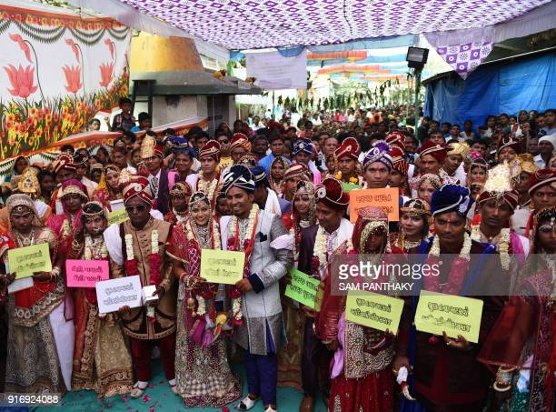 Indian couples pose for a photograph during a mass wedding for members of the Adivasi Bhil tribal community in Ahmedabad on February 11 2018 Some 35...