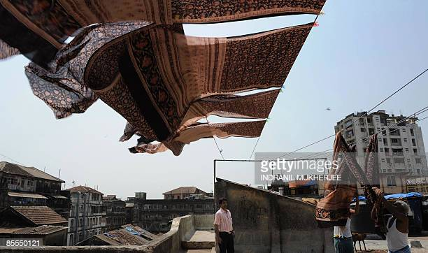Indian craftsmen are watched by factory owner Sarfraz Khatri as they dry a block print fabric made using natural dyes at the printing unit of...
