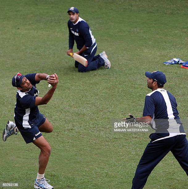 Indian cricket captain Anil Kumble catches the ball as teammate VVS Laxman and fielding coach Robin Singh look on during a training session at The...