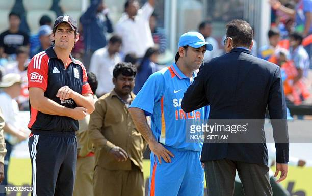 Indian cricket captain Mahender Singh Dhoni speaks to the commentator Ravi Shasthri as England captain Alaister Cook looks on during the first One...