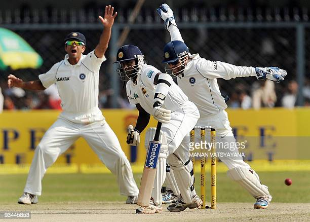 Indian cricket captain Mahendra Singh Dhoni and teammate Rahul Dravid celebrate the dismissal of Sri Lankan cricketer Ajantha Mendis on the fourth...