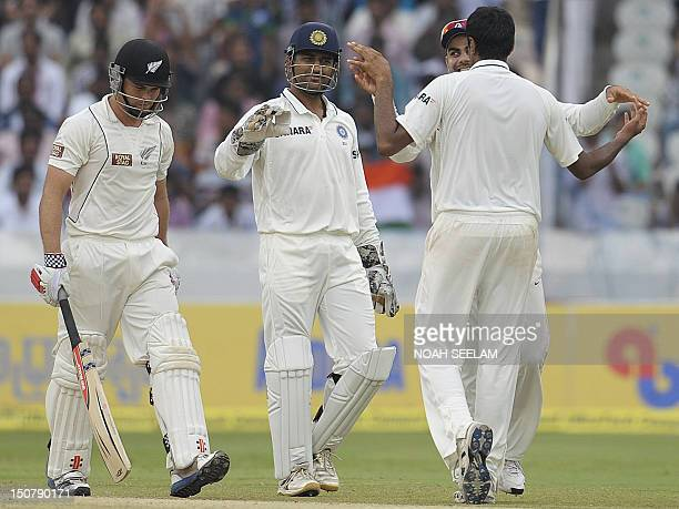 Indian cricket captain Mahendra Singh Dhoni celebrate with Ravi Chander Ashwin for taking the wicket of New Zealand criketer Daniel Flynn during the...