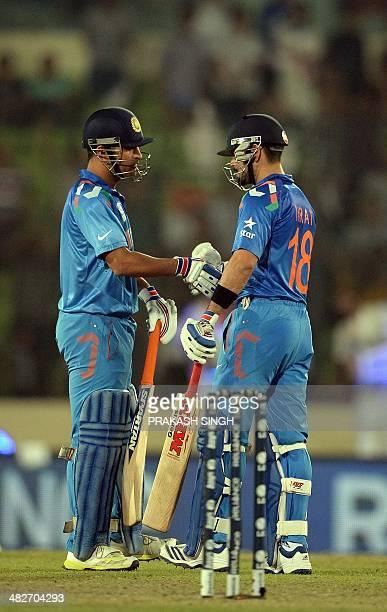 Indian cricket captain Mahendra Singh Dhoni congratulates batsman Virat Kohli after victory over South Africa during the ICC World Twenty20 cricket...
