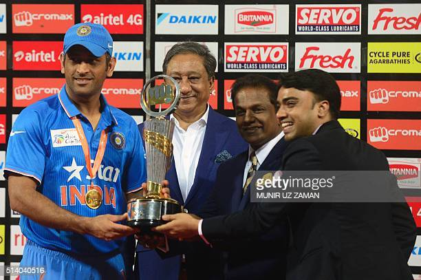 Indian cricket captain Mahendra Singh Dhoni holds the champion trophy after the Asia Cup T20 cricket tournament final match between Bangladesh and...