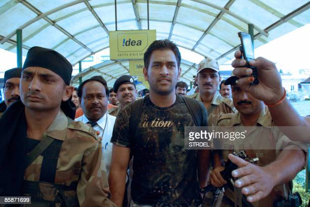 Indian cricket captain Mahendra Singh Dhoni is escorted by security personnel as he arrives at an airport in Ranchi on April 9 after returning from...