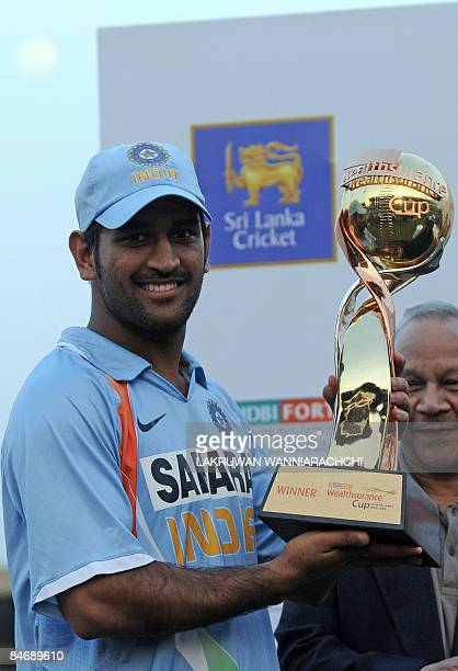 Indian cricket captain Mahendra Singh Dhoni poses with the winners trophy following the fifth and final One Day International match between India and...