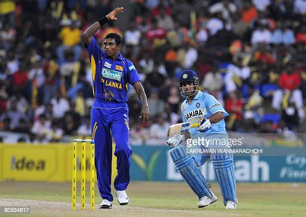 Indian cricket captain Mahendra Singh Dhoni runs between wickets as Sri Lankan cricketer Thilina Thushara Mirando looks on during the third One Day...