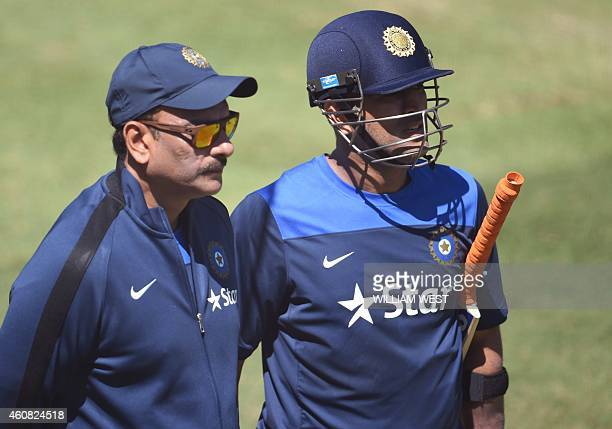 Indian cricket captain MS Dhoni speaks with team manager Ravi Shastri during training at the Melbourne Cricket Ground on December 25 2014 Australia...