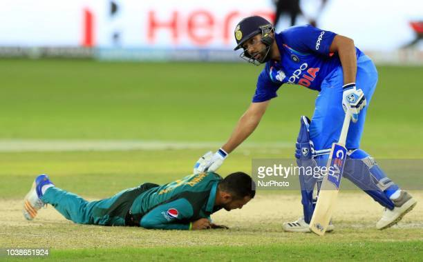 Indian cricket captain Rohit Sharma looks down at Pakistan's Mohammad Nawaz who falls down losing his balance during the Asia Cup 2018 cricket match...