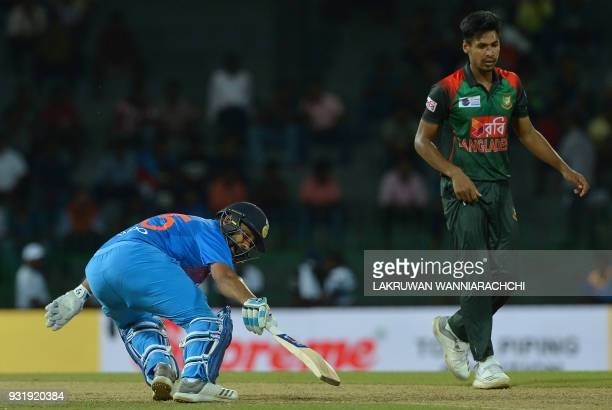 Indian cricket captain Rohit Sharma runs between the wickets as Bangladesh cricketer Mustafizur Rahman look on during the fifth Twenty20...