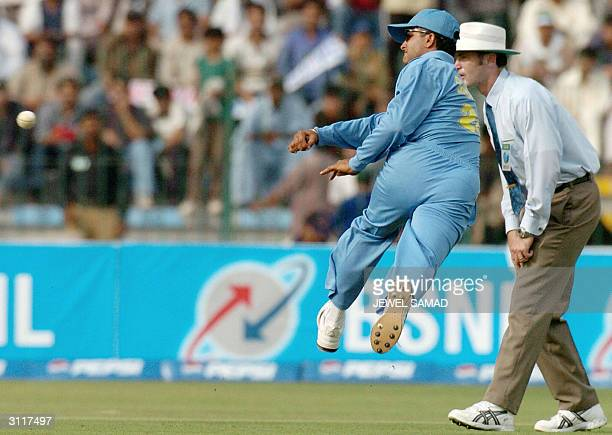 Indian cricket captain Sourav Ganguly is watched by umpire Simon Taufel as he jumps in the air while fielding a ball hit by his Pakistani counterpart...
