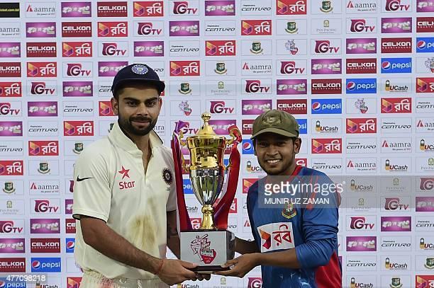 Indian cricket captain Virat Kohli and Bangladesh cricket captain Mushfiqur Rahim pose for a photograph with the tournament trophy following the...