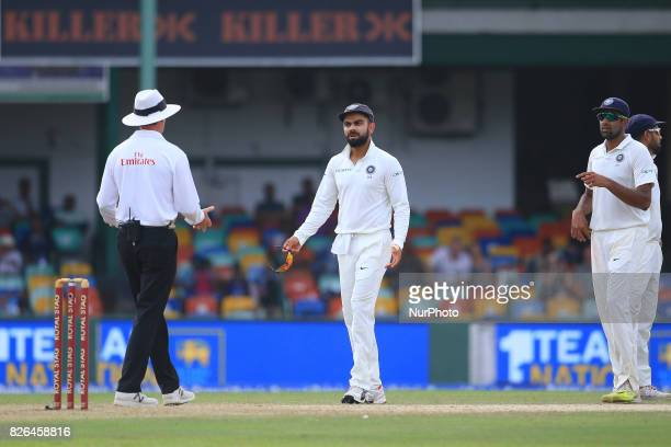 Indian cricket captain Virat kohli and Indian cricketer Ravichandran Ashwin discuss with the on field umpire about a turneddown appeal after Kohli...