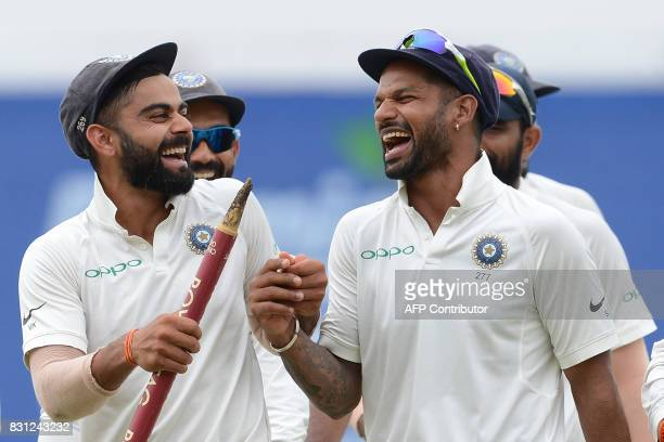 Indian cricket captain Virat Kohli celebrates with his teammate Shikhar Dhawan after their victory in the third and final Test match between Sri...