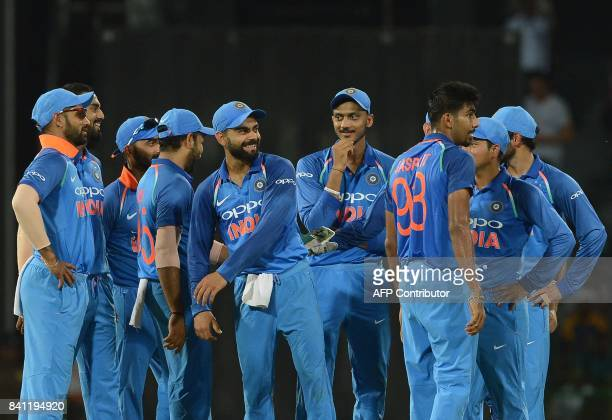 Indian cricket captain Virat Kohli celebrates with his teammates after dismissing Sri Lankan cricketer Dilshan Munaweera during the fourth one day...