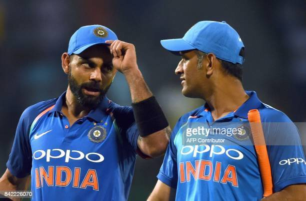 Indian cricket captain Virat Kohli celebrates with teammate Mahendra Singh Dhoni after victory in the final one day international cricket match...