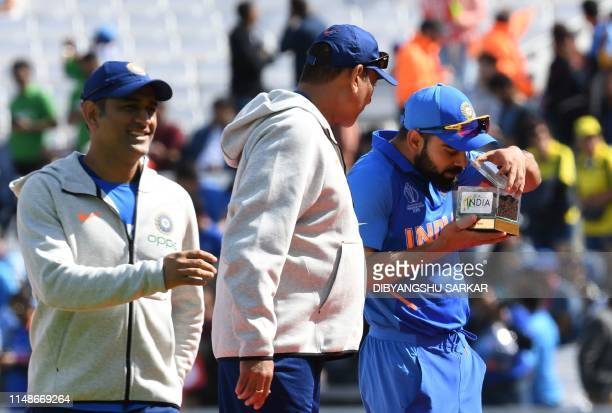 Indian cricket captain Virat Kohli is watched by India's Mahendra Singh Dhoni and India's head coach Ravi Shastri as he smells a box with Indian soil...