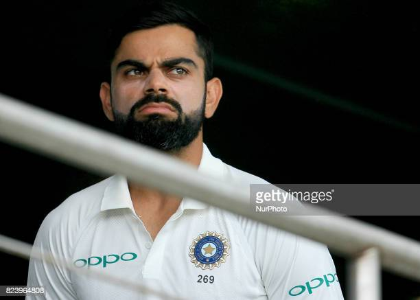 Indian cricket captain Virat Kohli looks on from the Indian team's dressing room after rain interrupted the 3rd Day's play in the 1st Test match...