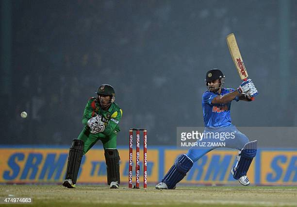 Indian cricket captain Virat Kohli plays a shot as Bangladeshi wicketkeeper Anamul Haque looks on during the second match of the Asia Cup oneday...