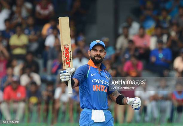Indian cricket captain Virat Kohli raises his bat to the crowd after scoring a century during the fourth one day international cricket match between...