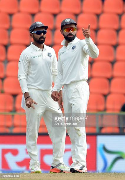 Indian cricket captain Virat Kohli speaks with teammate Ajinkya Rahane during the second day of the third and final Test match between Sri Lanka and...