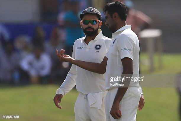 Indian cricket captain Virat Kohli talks to his team mate Ravichandran Ashwin during the 2nd Day's play in the 1st Test match between Sri Lanka and...