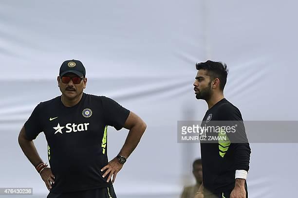 Indian cricket coach Ravi Shastri and captain Virat Kohli talk during a practice session at Khan Shaheb Osman Ali Stadium in Narayanganj on June 9...