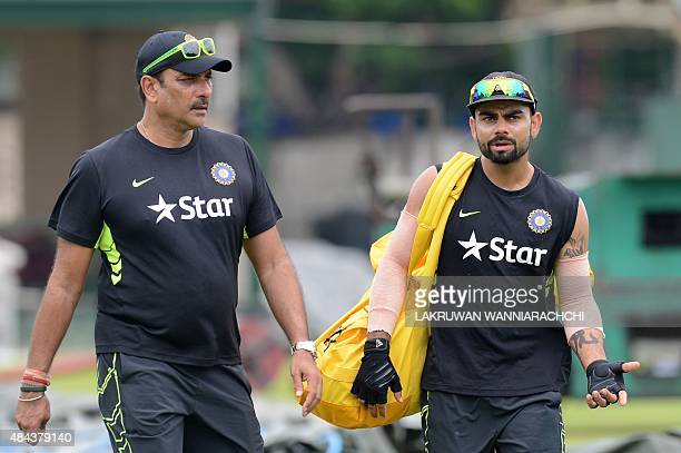 Indian cricket coach Ravi Shastri and captain Virat Kohli talk during a practice session at the P Sara Oval Cricket Stadium in Colombo on August 18...