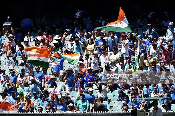 Indian cricket fans celebrate as batsman Virat Kohli reaches his century against Australia during the third oneday international cricket match...