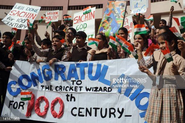 Indian cricket fans hold placards and posters as they celebrate after Indian cricketer Sachin Tendulkar scored his 100th century in the One Day...