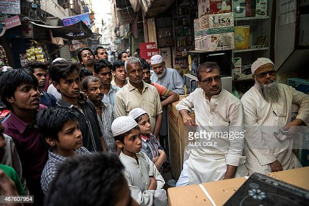 Indian cricket fans watch the Cricket World Cup semifinal match between India and Australia on the street in the old quarters of New Delhi on March...