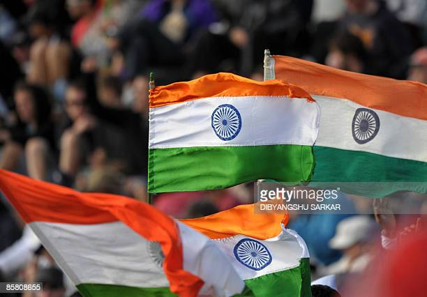 Indian cricket fans wave the Indian national flag to support the team during the second day of the final Test match between New Zealand and India at...