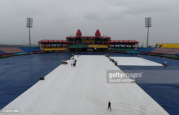 Indian cricket officials walk on the pitch after it was covered at the Himachal Pradesh Cricket Association Stadium during rainfall in Dharamsala on...