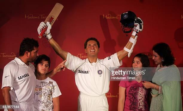 Indian cricket player Sachin Tendulkar his son Arjun daughter Sara and wife Anjali pose next to Sachin's wax figure in Mumbai India Monday April 13...