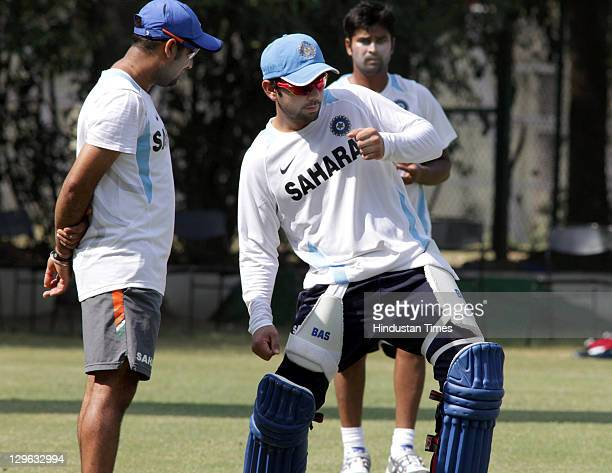 Indian cricket player Virat Kohli discuss some batting tips with other team members during the practice session at PCA stadium on October 19 2011 in...