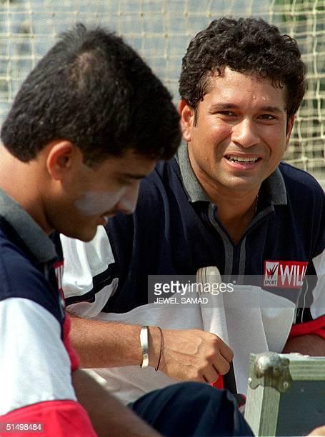 Indian cricket star batsman Sachin Tendulkar speaks with his team skipper Sourav Ganguly as they prepare to practice batting at Bangabandhu National...