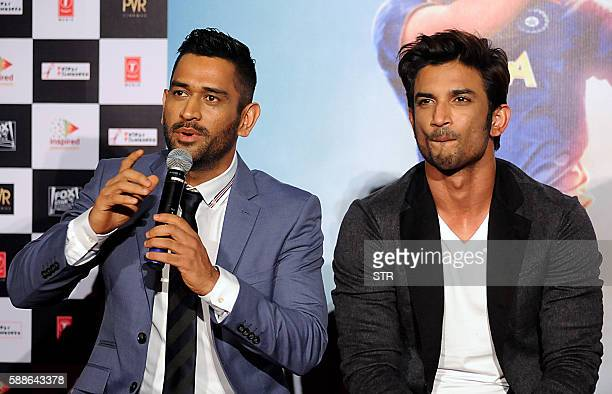 Indian cricket team captain Mahendra Singh Dhoni gestures as he speaks alongside Bollywood actor Sushant Singh while attending the trailer launch of...
