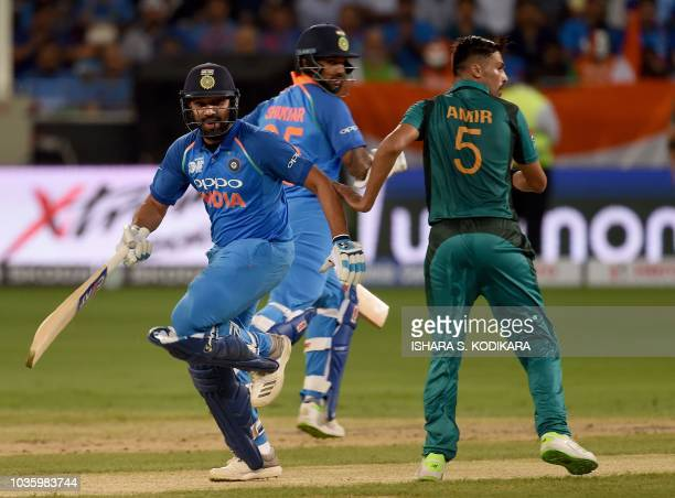 Indian cricket team captain Rohit Sharma and Shikhar Dhawan runs between the wickets as Pakistan cricketer Mohammad Amir looks on during the one day...