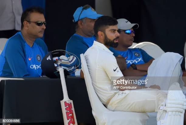 Indian cricket team captain Virat Kohli and newlyappointed coach Ravi Shastri look on during the first day of the twoday warmup match between Sri...