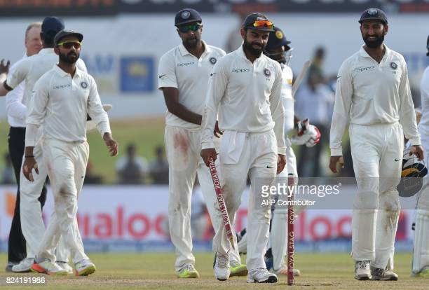 Indian cricket team captain Virat Kohli and teammates leave the pitch after the fourth day of the first Test match between Sri Lanka and India at...