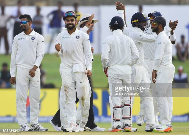 Indian cricket team captain Virat Kohli celebrates with his teammates after he dismissing Sri Lankan batsman Upul Tharanga during the second day of...