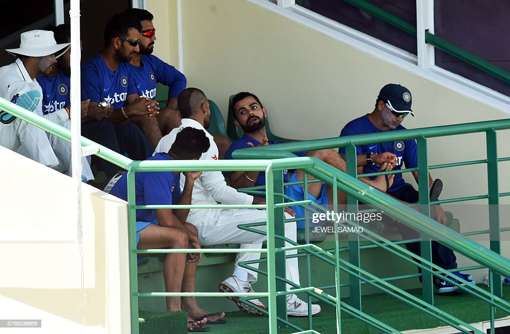 Indian cricket team captain Virat Kohli (C) chats with his teammates during Day 2 of the three-day tour match between India and WICB President's XI squad at the Warner Park stadium in Basseterre, Saint Kitts, on July 15, 2016. / AFP / Jewel SAMAD