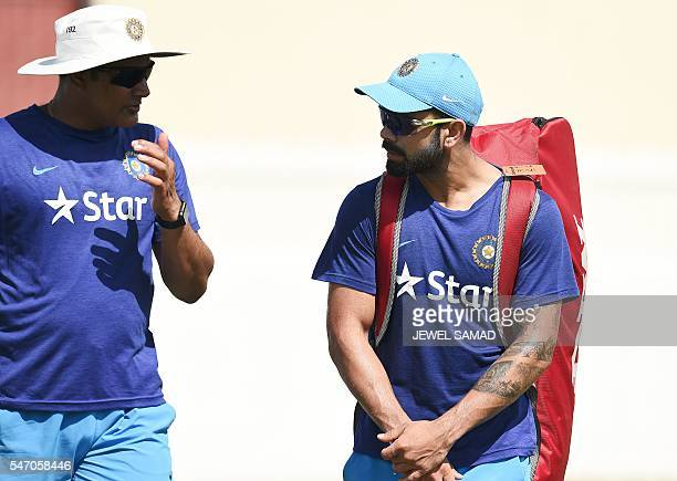 Indian cricket team captain Virat Kohli chats with team head coach Anil Kumble during a practice session at the Warner Park stadium in Basseterre...