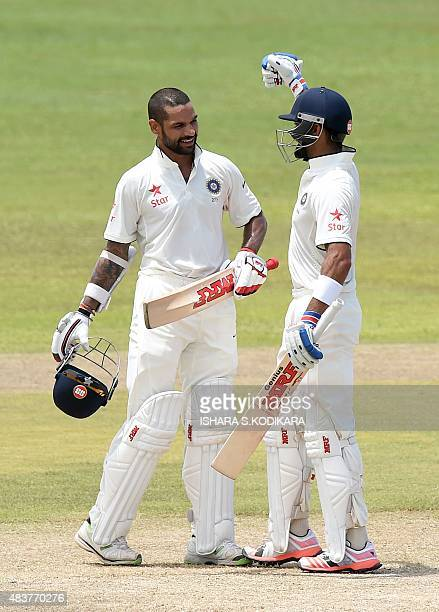 Indian cricket team captain Virat Kohli congratulates his teammate batsman Shikhar Dhawa on reaching a century during the second day of the opening...