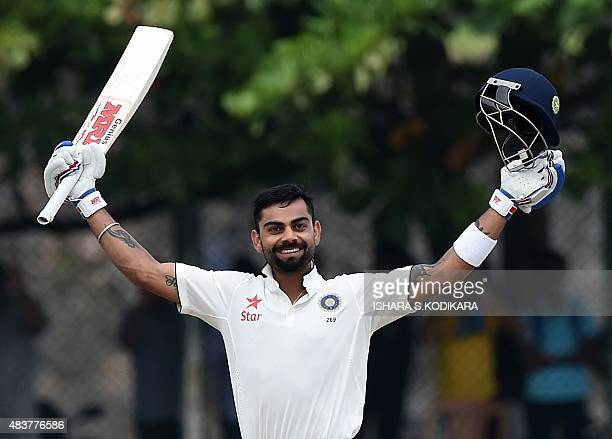 Indian cricket team captain Virat Kohli raises his bat after reaching a century during the second day of the opening Test match between Sri Lanka and...