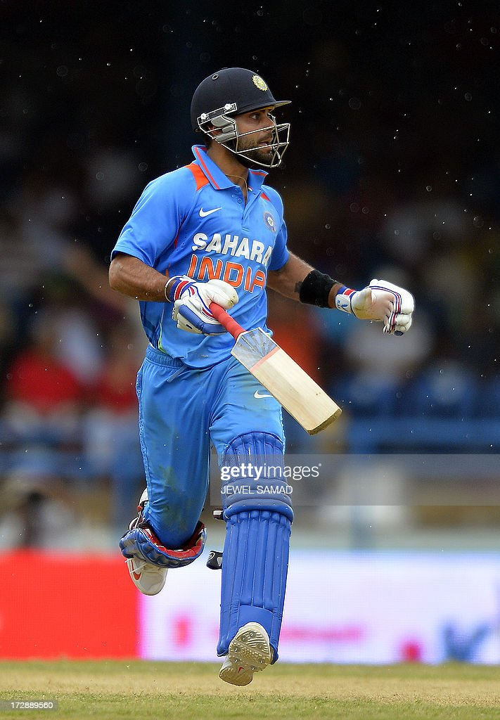 Indian cricket team captain Virat Kohli takes a run to complete his century during the fourth match of the Tri-Nation series between India and West Indies at the Queen's Park Oval in Port of Spain on July 5, 2013. India have scored 311/7 at the end of their innings. AFP PHOTO/Jewel Samad