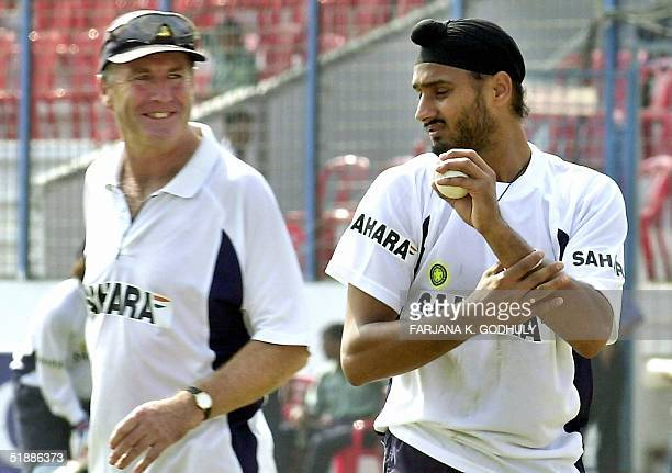 Indian cricket team coach John Wright smiles as he passes by his team spin bowler Harbhajan Singh during a practice session on the eve of the first...